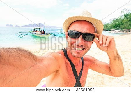 Travel man taking selfie on tropical beach at Palawan in Philippines Islands - Male funny self photo on blue lagoon tourist tour - Concept of happy moment in paradise destination around world