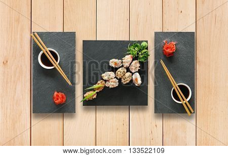 Japanese food restaurant, sushi gunkan plate or platter set. Set for two with chopsticks, ginger, soy, wasabi. Sushi at wooden planks background. Top view, flat lay.