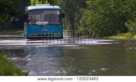 CHERKASSY, UKRAINE- JUNE 5, 2016: Bus driving on a flooded road during a flood caused by heavy rain, in Cherkassy.