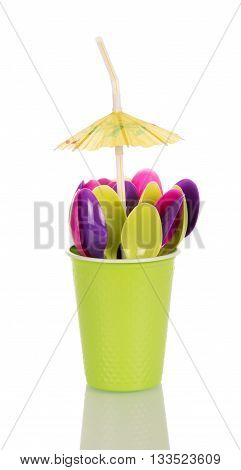 Green colored disposable cup with plastic spoon and an umbrella isolated on white background.