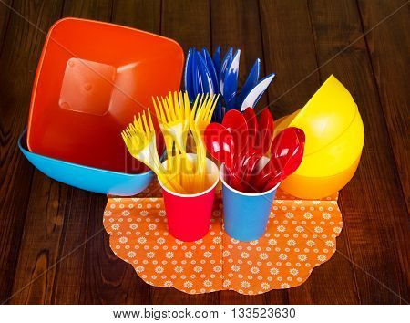Bright plastic tableware: bowls, forks, spoons, knives, and paper cups on the background of dark wood.