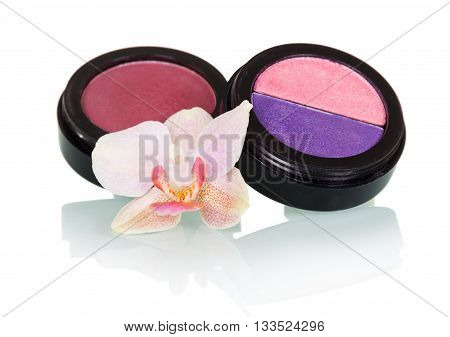 Jars eye shadow, lip gloss and orchid flower isolated on white background.