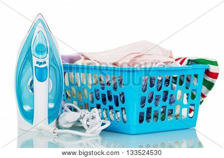 Steam iron and a basket of linen for ironing isolated on white background.