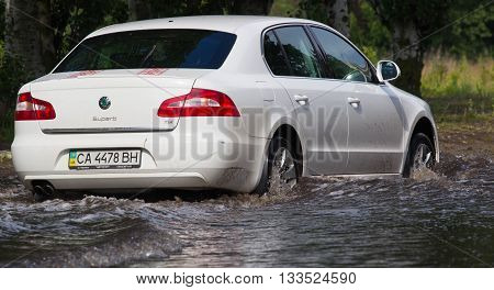 CHERKASSY, UKRAINE- JUNE 5, 2016: cars driving on a flooded road during a flood caused by heavy rain, in Cherkassy.