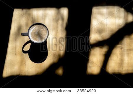 High Angle Still Life View of Single Cup of Frothy Coffee in Mug Served on Wooden Table and Illuminated in Dramatic Sunlight Streaming Through Window with Shadow of Tree Reflection