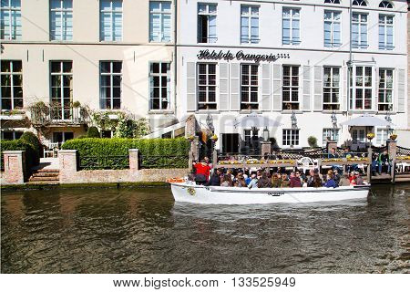 Bruges, Belgium - April 10, 2016: Boat tour station with tourists at canal in Bruges, Belgium