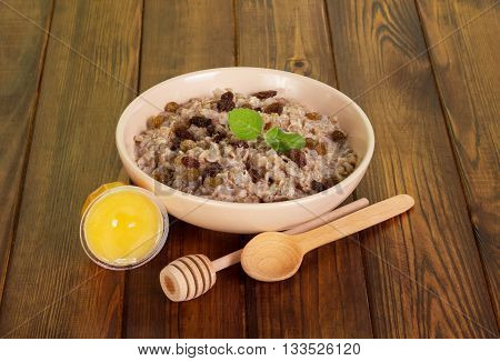 A bowl of oatmeal with raisins, honey and wooden spoons on dark wooden background.