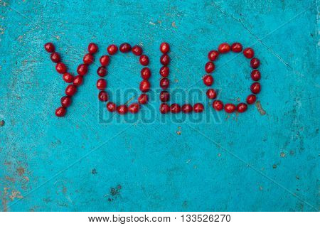 Cherries arranged to form the word YOLO on textured blue background