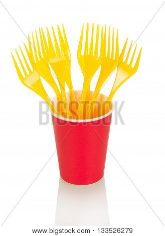 Red disposable cup and yellow plastic forks isolated on white background.
