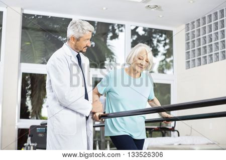 Doctor Looking At Senior Woman Walking Between Parallel Bars