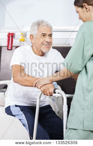 Nurse Assisting Patient To Stand In Rehab Center