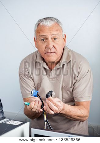 Confused Senior Man Holding Computer Cables In Class