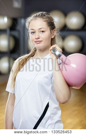 Attractive Determined Woman Lifting Kettlebell In Gym