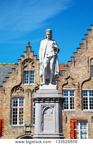 Statue of Hans Memling and traditional medieval house exterior against blue sky in Brugge, Belguim