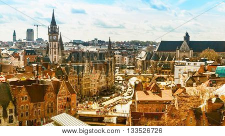 Ghent, Belgium - April 12, 2016: Aerial panoramic cityscape view of Ghent, Belgium with St. Michael Bridge, canal, medieval houses, church, clock tower against cloudy blue sky