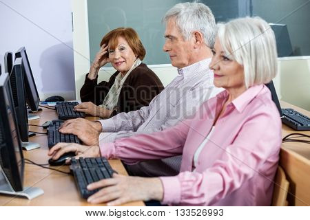 Smiling Senior Woman With Classmates At Computer Desk