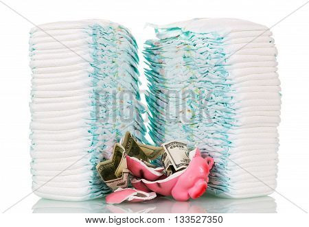 Piles of children's disposable diapers, broken piggy bank and money isolated on white background.