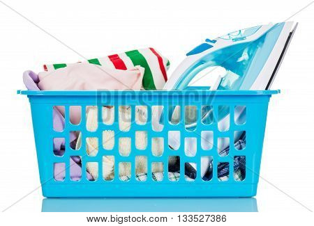 Basket with linen and ironing steam iron isolated on white background.