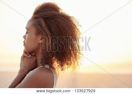 Beautiful young woman with her eyes closed standing on a beach at dusk