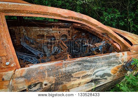 Rusty & burnt out car showing damage inside