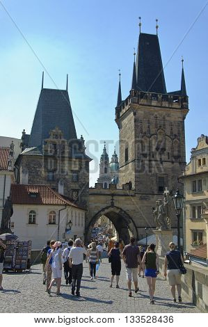 Prague Czech - 03 July 2015: Praguers and tourists exit the Charles Bridge through the arch of Lesser Town Tower.
