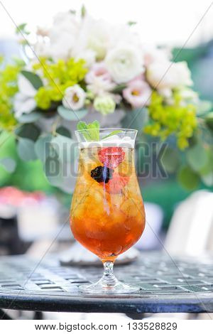 Ice tea in glass with ice, sliced strawberries and blackberries