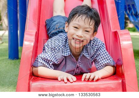 Young Asian boy playing slider at playground