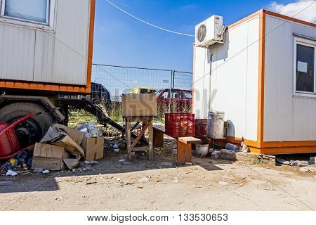 Workers place for eating among office containers near building site.
