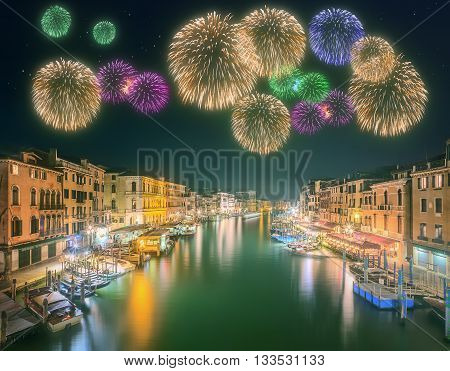 Beautiful fireworks under Grand Canal, boats and buildings from the bridge in Venice, Italy