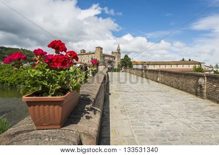 Monastero Bormida Italy - May 29 2016: Bridge people flowers houses and Church of Monastero Bormida in Piedmont Italy