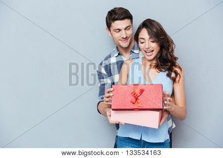 Young beautiful woman receiving a gift from her boyfriend isolated on gray background