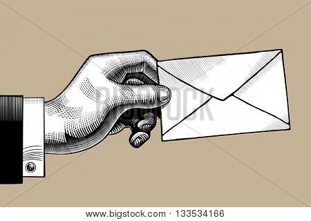 Hand with a Postal envelope. Hand with a mail. Retro style mail sign and icon. Vintage engraving stylized drawing. Vector illustration
