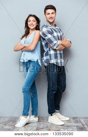 Attractive teenage couple standing back to back with arms crossed isolated on gray background