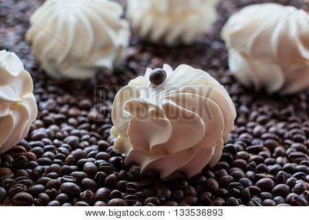 Sweet dessert - large vanilla marshmallows  on a wooden table with coffee beans, selective focus