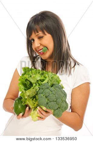 Young woman holding broccoli avocado and lettuce salad isolated on white background blinking with one eye