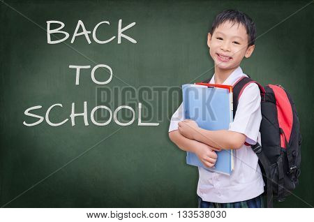Asian schoolboy in uniform stand in front of blackboard
