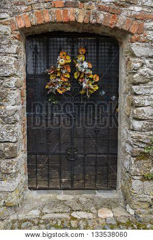 Old wooden door with flowers in Mombaldone in Piedmont Italy.