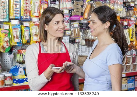 Saleswoman Accepting Payment From Female Customer In Pet Store