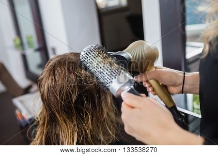 Hairdresser Styling Client's Hair In Salon