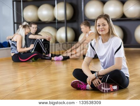 Woman Smiling While Sitting Crossed Legged On Floor At Gym