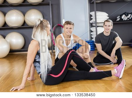 Men Looking At Female Friend Resting In Gym