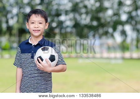 Young Asian boy with ball in park