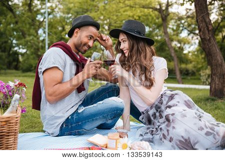 Smiling young couple having picnic and drinking wine outdoors