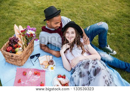 Relaxed young couple lying and having picnic on lawn