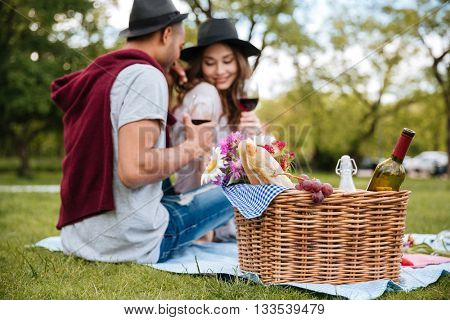 Basket with food and drinks standing near tender young couple drinking wine in park