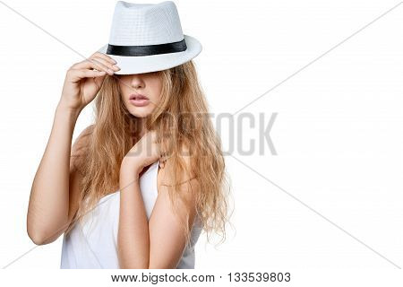 Closeup of beautiful slytish woman posing in fedora hat covering eyes, over white background
