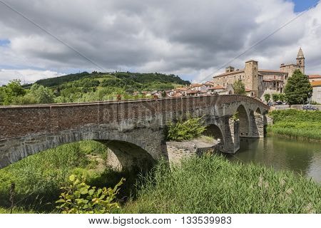 Roman Bridge people river Bormida houses and Church of Monastero Bormida in Piedmont Italy