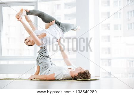 Beautiful young woman stretching and doing acro yoga with partner in studio
