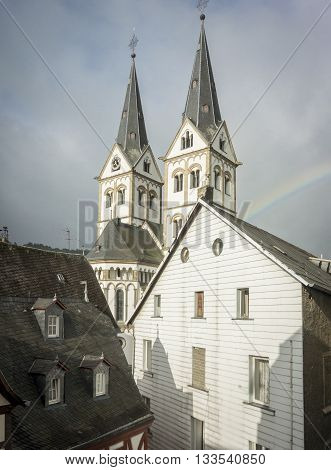 The church steeples of Saint Severus's Church in Boppard Germany with a rainbow after the storm
