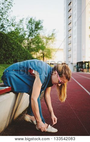 Young woman tying a shoelace on the bench at the race track